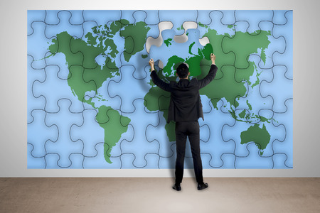 Man hold puzzle of world map attach on the wall photo