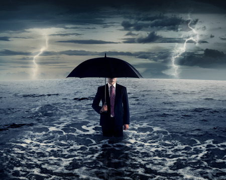 weather protection: Business man standing on the sea in the middle of storm