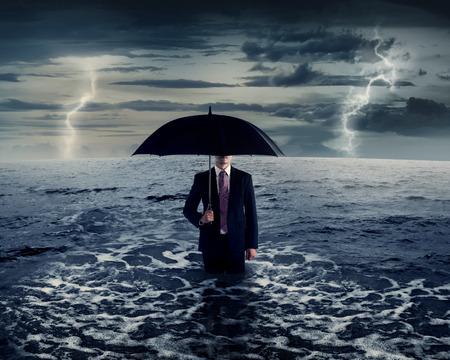 uomo sotto la pioggia: Business uomo in piedi sul mare nel mezzo della tempesta
