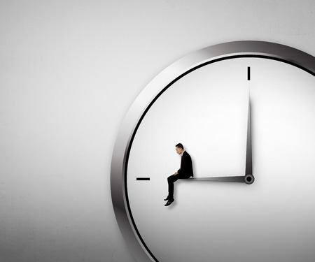 Business man sitting on the clock. Overtime conceptual image