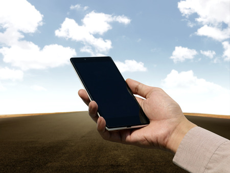Hand holding cellphone with blank screen on empty road background. You can put your design on the cellphone photo