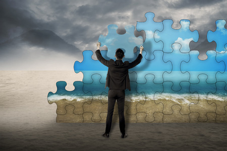 strategy decisions: Business man holding puzzle to assembly change situation from desert to sea shore