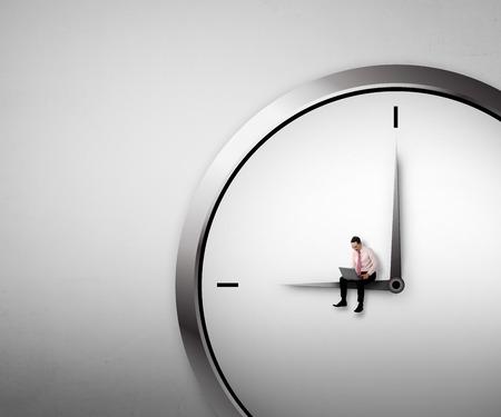 時計の上に座ってのビジネスマン。残業の概念