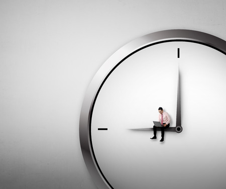 job deadline: Business man sitting on the clock. Overtime conceptual Stock Photo