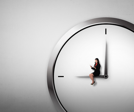 overtime: Woman sitting on the clock using tablet. Overtime conceptual