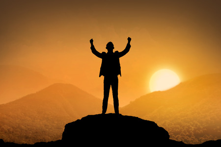 business suit: Silhouette business man standing top of the mountain when sunset come
