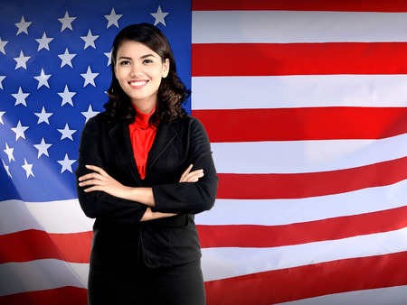 asian american: Business woman folding hand over USA flag. Working in USA concept Stock Photo