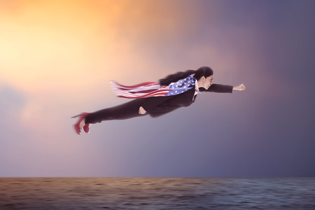 american hero: Woman flying over the ocean wearing USA flag cape Stock Photo