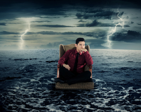 Business man sitting on armchair in the ocean water. Danger concept. photo