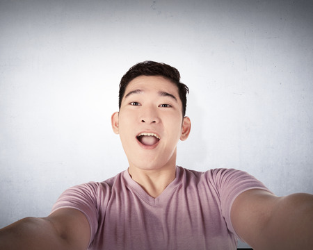 asian man face: Handsome young man holding camera and making selfie isolated over grunge wall background Stock Photo