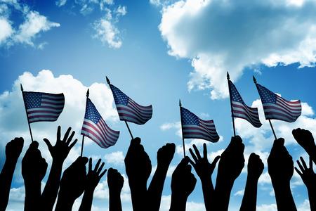 gente saludando: Grupo de personas que ondeaban peque�a bandera EE.UU. enfrenta el cielo azul