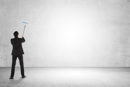 hombre pintando: Hombre de negocios que pinta algo en la pared vac�a. Usted puede poner su dise�o aqu�