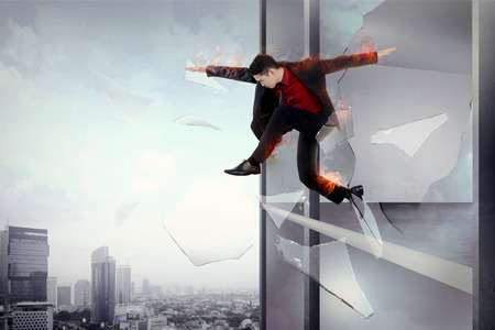 risky business: Man escape from office through window with flame all over body. Risky business conceptual Stock Photo