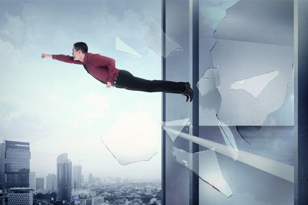 flying man: Business man flying through office building window. Business freedom conceptual