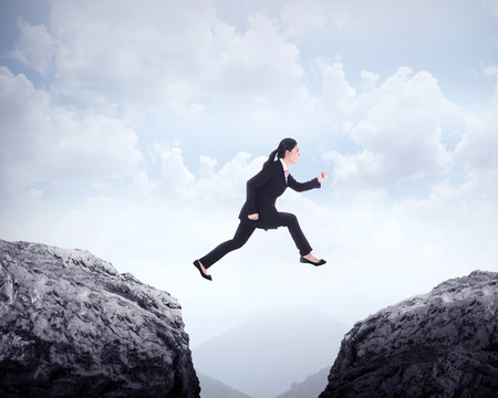 challenges: Business woman jumping across hill. Business challenge conceptual