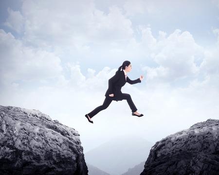obstacle: Mujer de negocios saltando a través de la colina. Desafío conceptual de negocios
