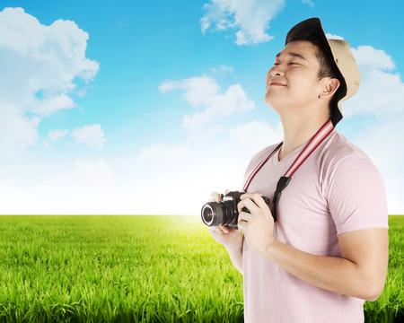 Azjatycki turysta zrobić zdjęcie na zielonej łące. Koncepcja wakacji letnich