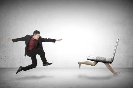 Business man chasing laptop. Chasing your job conceptual Stock Photo