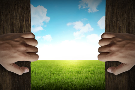 緑の草の牧草地に男の手のオープンドア