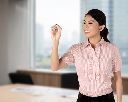 Asian woman writing something on the office photo