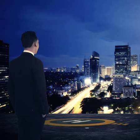 urban transport: Business man standing on rooftop helipad. Looking at the city. Business success concept