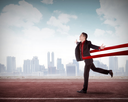 Concept of successful asian business man in a finishing line