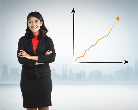 sales chart: Successful asian business woman over increasing sales chart on the background