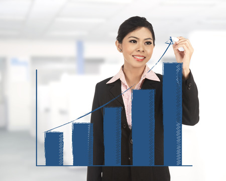 increasing: Business woman draw increasing chart wit office background