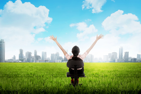 indonesian people: Backview of asian business woman sitting on chair on the meadow Stock Photo