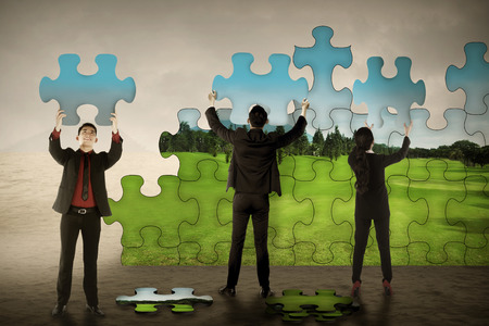 team problems: Business teamwork assembling puzzle pieces create green environtment. Green industry concept