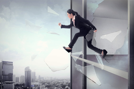 risky business: Business woman jump through office window glass. Business freedom concept