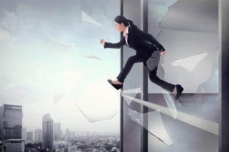 libertad: Mujer de negocios que saltar a través de cristal de la ventana de la oficina. La libertad comercial concepto Foto de archivo