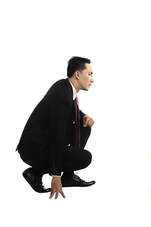 squatting: Asian business man squat isolated over white background
