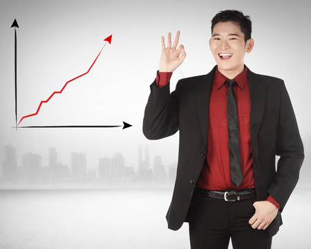 give hand: Asian business man give hand gesture OK with increase chart background