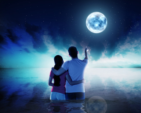 man in the moon: Young couple ponting moon at night time in the sea