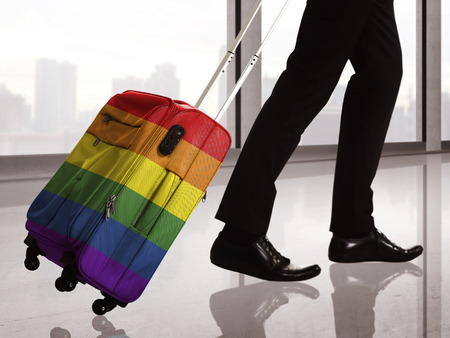 gay symbol: Suitcase with LGBT flag pattern. Travel to gay legal country conceptual Stock Photo