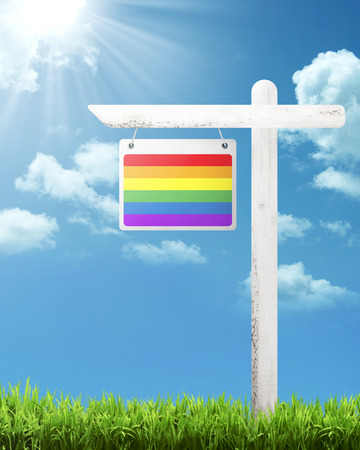 wooden post: Rainbow flag on wooden post with blue sky background