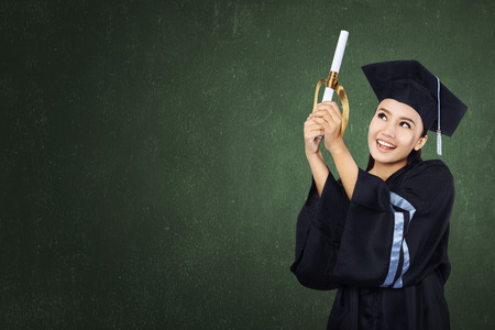 Happy graduated student girl with scroll on green chalkboard background