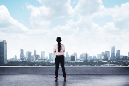 Asian business woman looking to the city from rooftop building Stock Photo