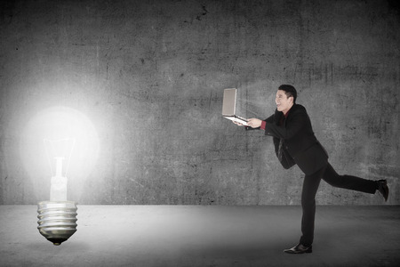performace: Business man run with laptop chasing light bulb. Making idea conceptual