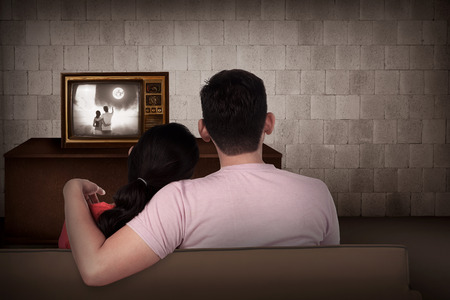 looking at watch: Young asian couple watching retro tv in the house