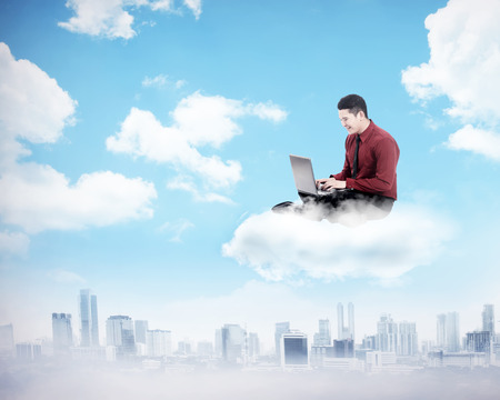cloud computer: Business man working on the cloud above the city. Cloud computing concept
