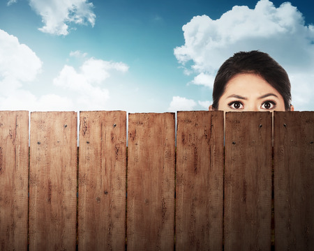 fence: A woman head behind wooden fence with blue sky background Stock Photo