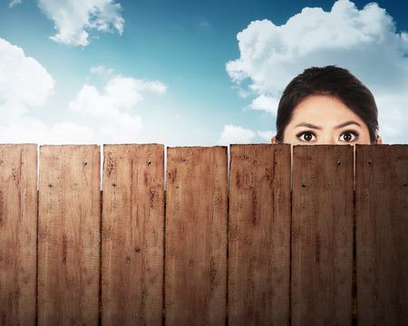 Een vrouw het hoofd achter houten omheining met blauwe hemel achtergrond