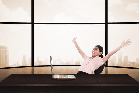 raise hand: Business woman sitting on the chair with raise hand and laptop. Business success concept