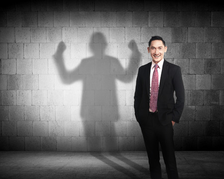 creative power: Asian business man casting a shadow of strength career concept