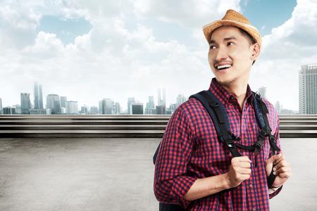 Azjatycki turysta nosić plecak uśmiechnięty, gdy podróżujesz po mieście Zdjęcie Seryjne