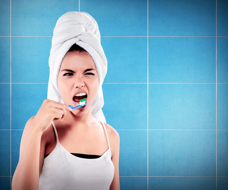 Woman with great teeth holding tooth-brush on bathroom background Stock Photo