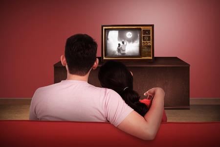 viendo television: Joven que ve la TV retra en la casa pareja asi�tica Foto de archivo