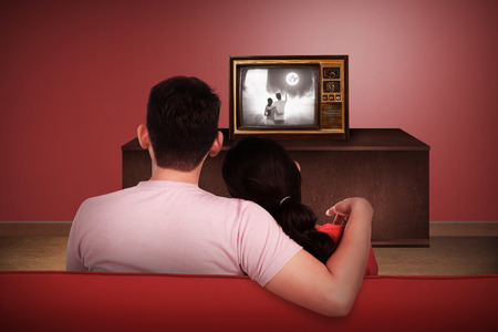 woman watching tv: Young asian couple watching retro tv in the house